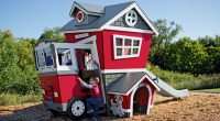 children's cubby house in shape of fire station with slide and dog house at side