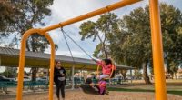 Arched Swing frame with friendship swing seat that has people riding sitting facing each other
