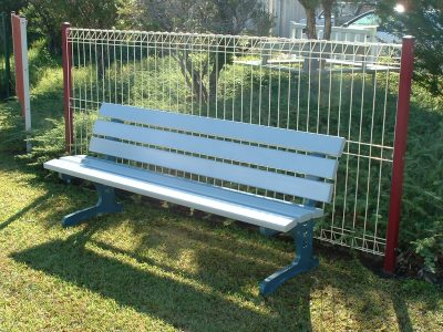 Outdoor seat in park with white slats and back rest in front of a metal fence