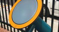 outdoor musical drum with aqua frame and orange rim around drum face