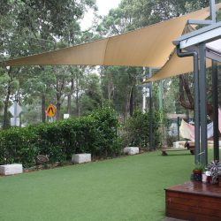 Triangular Shade sails over open synthetic grass area