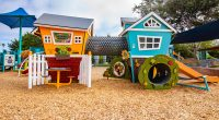 children's cubby units with two houses linked with a tunnel, featuring slide and white picket fence