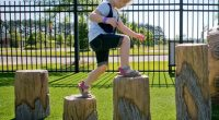 young girl balancing while walking across different logs of different heights