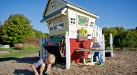 Child's cubby unit with slide and market stall features