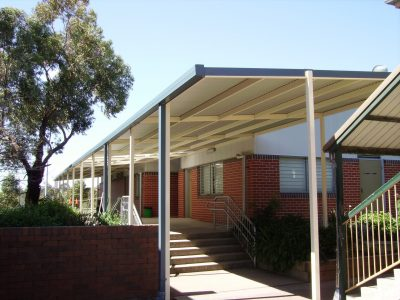Skillion awning used for walkway over long concrete corridor leading to stairway