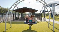 arched silver frame with large circular bucket seat that holds multiple children while they are swinging