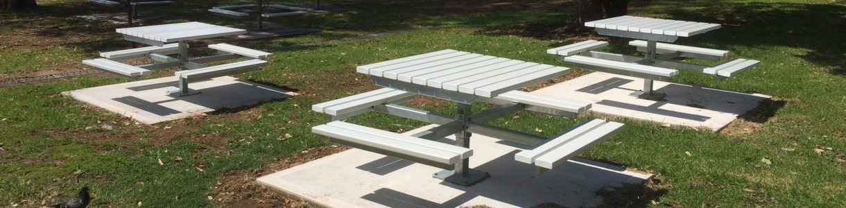White 4 Way Picnic Settings on concrete slabs in school yard