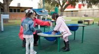 children playing with water at a table splashing water in the different levels