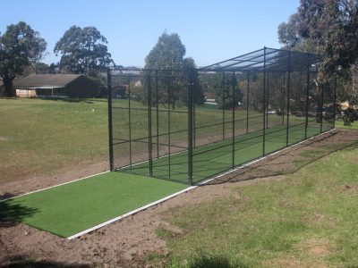Cricket Cage in school yard with synthetic grass pad and concrete edging
