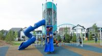 Tall tower structure with Cylinder shape with high double slide, tube slide and ground level spinners and climbers