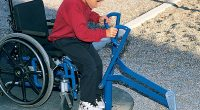 boy in wheelchair playing in the sand using an accessible digger to scoop up the sand