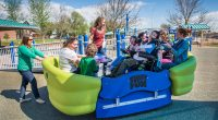 Rocking boat for playground with wheelchairs and a number of children and carers riding on the equipment