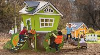 Green cubby house with boy climbing up ladder