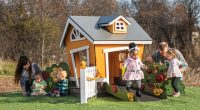 Orange cubby house with young girl in pretty pink dress standing infront
