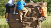 Large rock structure with children climbing up the sides