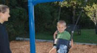 young child in a swing seat with a blue frame