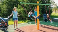 toddler swing set with T shape frame and small child swinging being pushed by mother
