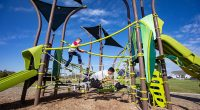 Tall climbing structure with two slide sand built in shade sails, features climbing nets and nature colour theme