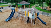 Play structure with lots of activities for kids with silver posts and two large blue slides