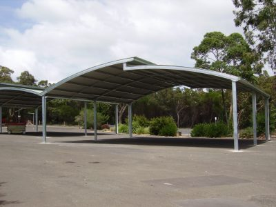 Large Rolled roof shelter over basketball court area with breezeway to allow airflow