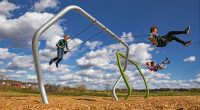 swing set with a modern twisted frame with kids swinging high up in to the sky