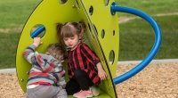 circular climber with green panels and blue support rail with toddlers climbing over it