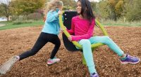 girl sitting in a spinning chair with another girl pushing her around in circles