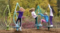 children spinning around on platforms with high curvy frames to hold on to
