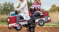two young girls riding on a fire engine spring toy in tandem