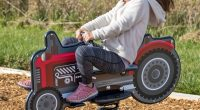 girl riding on spring toy with tractor graphics