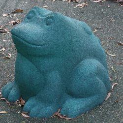 Rubber frog statue in blue colour surrounded by leaves