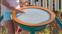 Large round drum shaped like a kettle with girls hands hitting drum