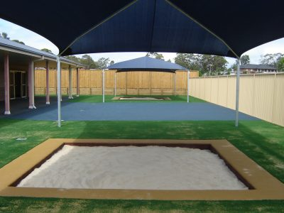 Inground sandpit under shade structure with rubber wetpour border and synthetic grass