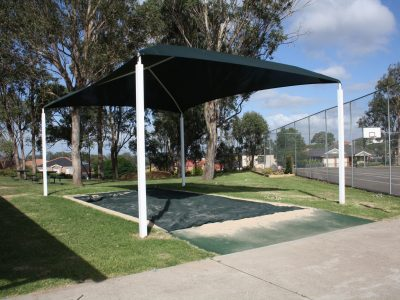 Inground sandpit under shade structure with sandpit cover and rubber wetpour entry